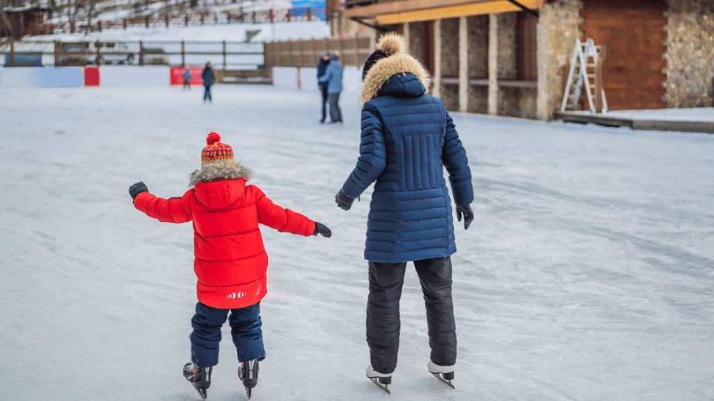 A girl with mom ice skating